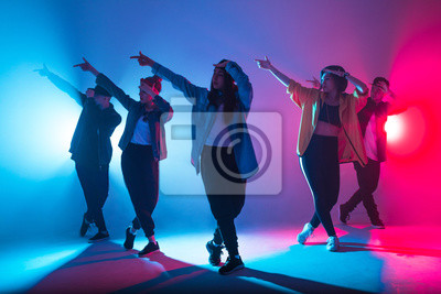 Obraz Young modern dancing group of six adult young people practice dancing on colorful background