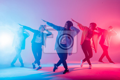 Obraz Young modern dancing group of six adult young people practice dancing on colorful background. Fashionably dressed youngsters moving over blurred disco club color lights