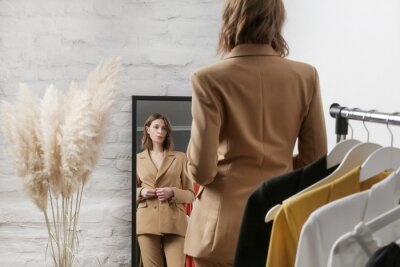Obraz Young woman choosing clothes and trying on beige blazer in fashion atelier or personal wardrobe.