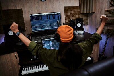 Obraz Young woman, female artist raising her arms while succeeding in creating music, sitting in recording studio