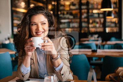 Obraz Young woman is drinking coffee in a cafe
