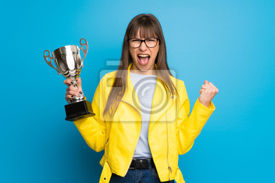 Obraz Young woman with yellow jacket on blue background holding a trophy