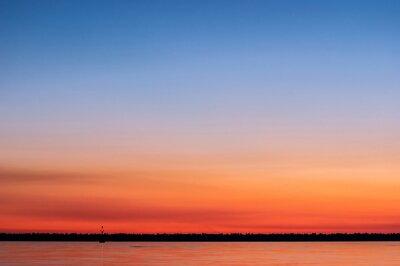 Zachód słońca na morzu z odcieniami pomarańczowego, magenta i niebieskim na niebie