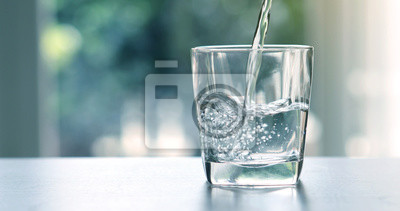 Obraz Zamknąć odlewania oczyszczone świeżego wody pitnej z butelki na stole w salonie