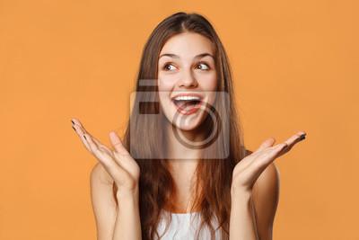 Obraz Zaskoczony szczęśliwy piękna kobieta, patrząc na boki w podnieceniu. Pojedynczo na pomarańczowym tle