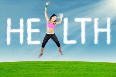 Obraz Zdrowa kobieta skacze z tekstem zdrowia w przyrodzie