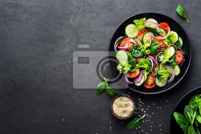 Obraz Zdrowa sałatka jarzynowa ze świeżych pomidorów, ogórków, cebuli, szpinaku, sałaty i sezamu na talerzu. Menu diety. Widok z góry.
