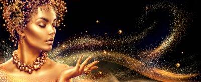 Obraz Złota kobieta. Beauty modelka dziewczyna złoty makijaż, włosy i biżuterię na czarnym tle