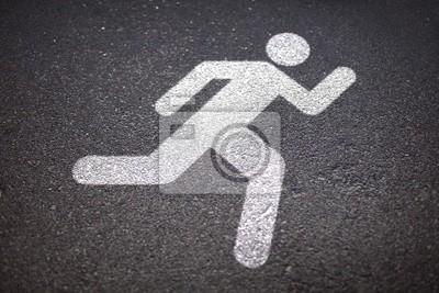 Znak biegacz na drodze asfaltowej