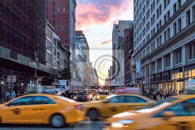 Żółte taxi taksówki przyśpiesza w dół Broadway podczas godziny szczytu w Manhattan, Miasto Nowy Jork z kolorowym zmierzchu niebem w tle