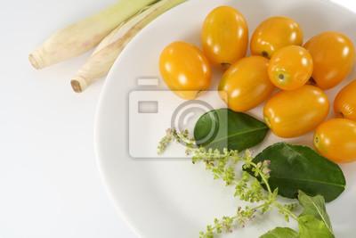Żółty pomidor / żółty pomidor wapnem kaffir liście na białym talerzu.