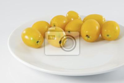 Żółty pomidor / żółty pomidorów cherry na białym talerzu.