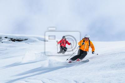 Obraz Zwei Skifahrer befahren gemeinsam einen steilen Hang