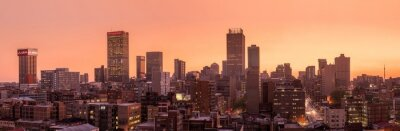 Plakat A beautiful and dramatic panoramic photograph of the Johannesburg city skyline, taken on a golden evening after sunset.