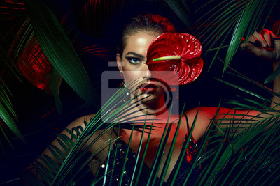 Plakat A beautiful tanned girl with natural make-up and wet hair stands in the jungle among exotic plants.