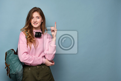 Plakat A blue-eyed girl with a backpack, headphones on her neck stands on a blue background and points her finger to the top.