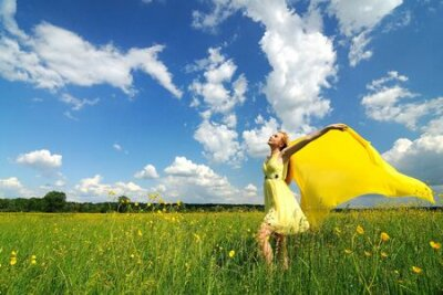 Plakat A girl in a yellow dress poses with hands up in a green field with a silk cloth in her hands. Beautiful outdoor photo