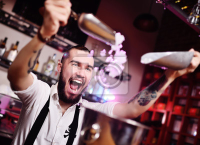 Plakat a handsome bearded bartender in a white shirt pours ice for cocktails and screams happily against the bar at a nightclub party