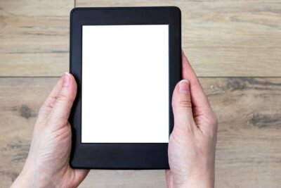 Plakat A modern black electronic book with a white blank screen in female hands against a blurred wooden tile floor background. Mockup tablet closeup