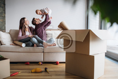 Plakat A portrait of young couple with a baby and cardboard boxes moving in a new home.