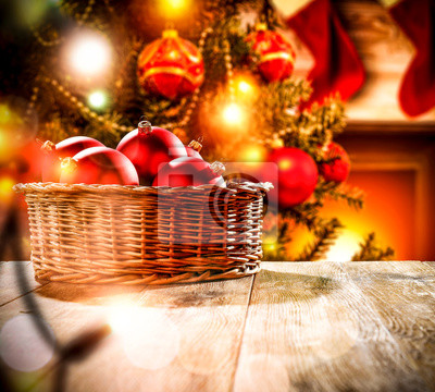 A wooden table with space for your advertising products. Blurred great green Christmas tree and Fireplace with flames and red socks of Santa Claus background.