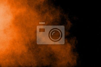 Plakat Abstrakcjonistyczny pomarańcze proszka wybuch na czarnym tle. Zablokuj ruch rozprysków cząstek pyłu pomarańczowego.