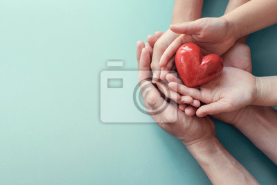 Plakat adult and child hands holding red heart on aqua background, heart health, donation, CSR concept, world heart day, world health day, family day