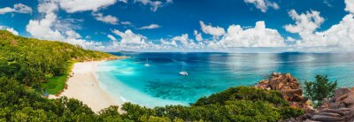 Plakat Aerial Pano of Grand Anse beach at La Digue island in Seychelles. White sandy beach with blue ocean lagoon and catamaran yacht moored