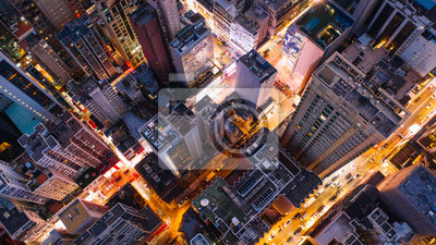 Plakat Aerial top view of downtown district  buildings in night city light. Bird's eye view from drone of cityscape metropolis infrastructure, crossing streets with parked cars. Development infrastructure