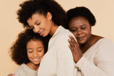 Plakat african american grandmother embracing with daughter and granddaughter with closed eyes isolated on beige