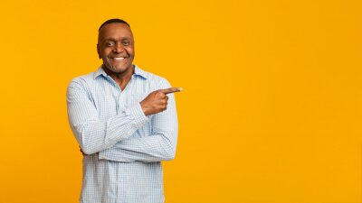 Plakat African american mature man pointing aside at empty space