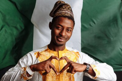 Plakat African man in national clothes and traditional headdress from Nigeria is making a heart by his fingers before the waving flag