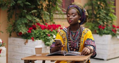 Plakat African pretty young woman in the traditional outfit talking on the phone cheerfully while sitting at the table wit magazine and coffee in the beautiful courtyard.