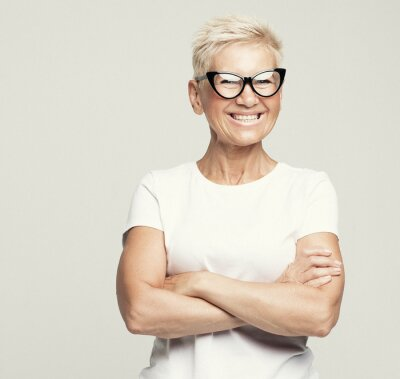 Plakat Aged people, lifestyle and maturity concept: blonde fifty year old European female with stylish pixie haircut and eyeglasses smiling at camera and posing isolated over grey background.