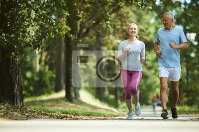 Plakat Aktywna i zdrowa para w wieku działa w środowisku naturalnym w letni poranek