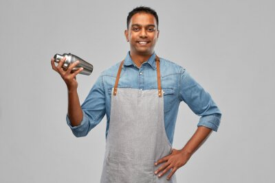 Plakat alcohol drinks, people and profession concept - indian barman in apron with cocktail shaker over grey background