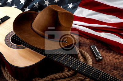 Plakat American culture, living on a ranch and country muisc concept theme with a cowboy hat, USA flag, acoustic guitar, harmonica and a rope lasso on a wooden background in a old saloon