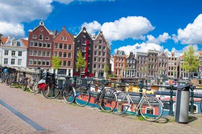Plakat Amsterdam, Holandia 27 kwietnia: Amsterdam miasta z domów mieszkalnych i rowerów zaparkowanych na moście w kwietniu 27.2015. Amsterdam jest najbardziej zaludnionym miastem w Królestwie Niderlandów.