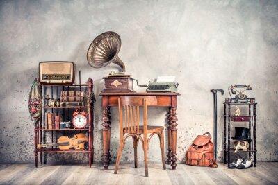 Plakat Antique chair, old typewriter, retro radio,  gramophone on wooden desk, books, clock, camera, binoculars, fiddle, keys on shelf, mask, cylinder hat, shoes, cane, backpack. Vintage style filtered photo