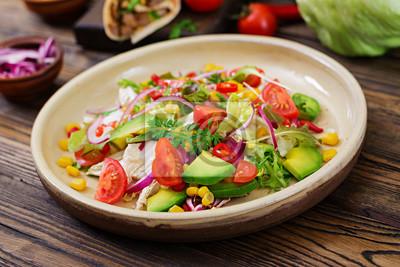 Apetyczna wegańska sałatka z pomidorów, awokado, kukurydzy, czerwonej cebuli i liści sałaty. Smaczne wegańskie jedzenie. Zdrowe wegańskie jedzenie. Sałatka wegetariańska.