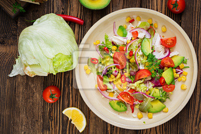 Apetyczna wegańska sałatka z pomidorów, awokado, kukurydzy, czerwonej cebuli i liści sałaty. Smaczne wegańskie jedzenie. Zdrowe wegańskie jedzenie. Sałatka wegetariańska. Widok z góry
