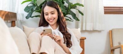 Plakat Asian beautiful girl using mobile phone, sitting in the living room.