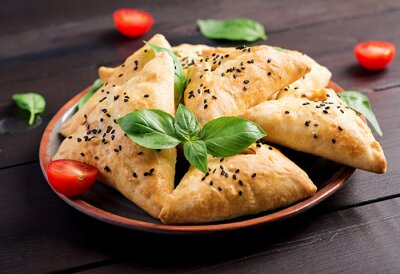 Asian food. Samsa (samosa) with chicken fillet and green herbs on wooden background.