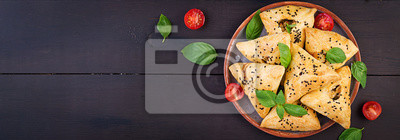 Asian food. Samsa (samosa) with chicken fillet and green herbs on wooden background. Banner. Top view