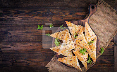 Asian food. Samsa (samosas) with chicken fillet and cheese on wooden background. Top view