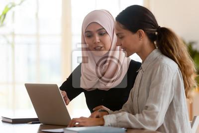 Plakat Asian muslim female mentor teaching caucasian intern explaining computer work
