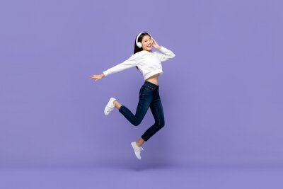 Plakat Asian woman jumping and listening to music on headphones