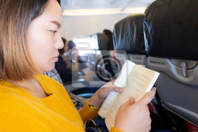 Plakat asian woman reading book on plane
