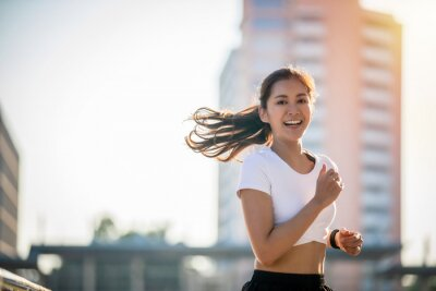 Plakat Asian Young fitness sport woman running  and smiling on city road
