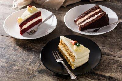Plakat Assortment of sweet cake slices. Chocolate, carrot and velvet cake slices on wooden table